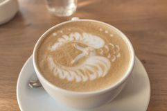 拿铁艺术有猫头鹰形状的浓咖啡杯子在一张木桌上的泡沫 库存照片