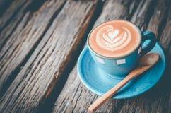 拿铁艺术,在木背景的蓝色咖啡杯 库存图片