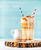 拿铁macchiato用在高玻璃的被鞭打的奶油和焦糖调味汁在蓝色的木板绘了墙壁背景 免版税图库摄影
