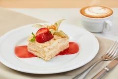 拿破仑蛋糕用草莓、空泡和果酱在白色板材 mille-feuille点心用咖啡和利器 库存图片