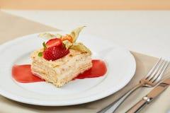 拿破仑蛋糕用草莓、空泡和果酱在白色板材 mille-feuille点心用新鲜的莓果和利器 免版税库存图片
