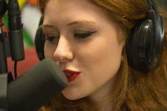 主持一个广播节目的俏丽的红头发人学生 免版税库存照片