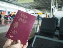 持一本比利时护照的人在机场终端 库存图片