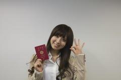 持与好标志的女商人日本护照 免版税库存图片