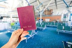 持与机场的妇女一本普通红色护照 免版税库存照片