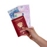 持与欧洲钞票的女性手一本护照 库存照片