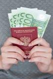 持与欧洲钞票的女性手一本护照 免版税图库摄影