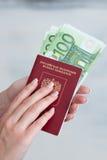 持与欧洲钞票的女性手一本护照 免版税库存图片