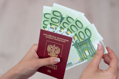 持与欧洲钞票的女性手一本护照 库存图片