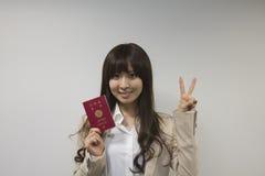 持与胜利标志的女商人日本护照 免版税图库摄影