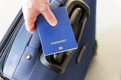 持在他的行李上的男性手一本护照 免版税库存照片