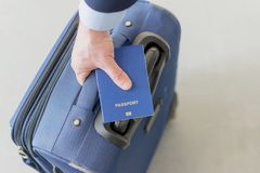 持在他的行李上的男性手一本护照 免版税库存图片