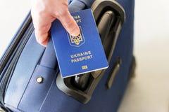 持在他的行李上的男性手乌克兰护照 库存照片