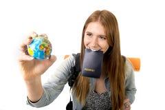 年轻持在嘴的学生旅游妇女护照搜寻拿着世界地球的旅行目的地 库存照片