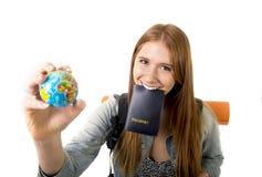 年轻持在嘴的学生旅游妇女护照搜寻拿着世界地球的旅行目的地 免版税库存照片