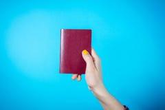 持护照的妇女的手反对蓝色背景 免版税库存照片