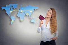 持护照的旅游少妇站立看世界地图 免版税图库摄影