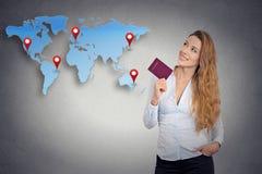 持护照的旅游少妇站立看世界地图 库存照片