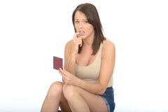 持护照的有关担心的紧张的少妇 免版税库存照片