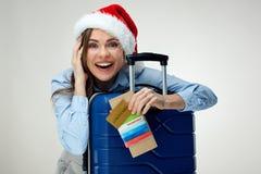 持护照,壁虱的微笑的妇女佩带的圣诞节圣诞老人帽子 免版税图库摄影
