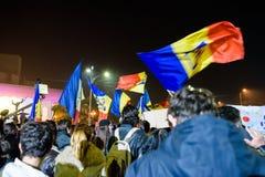挂罗马尼亚旗子的罗马尼亚人在示范 库存照片