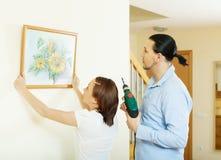 挂艺术图片的中年夫妇 免版税库存照片
