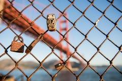 挂锁和篱芭和金门大桥在背景中在堡垒点,旧金山 免版税库存照片