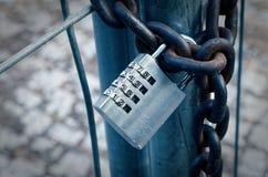 挂锁在一个建造场所以一个生锈的链子说明与一个数字代码的加密在减速火箭的神色 库存图片
