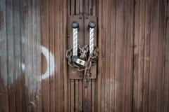 挂锁并且束缚安全地锁在生锈的门 图库摄影