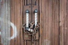 挂锁并且束缚安全地锁在生锈的门 库存照片