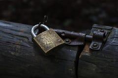 挂锁并且闩上巩固一个老木门 库存照片