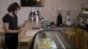 指令和支付他们的咖啡的女性和男性客户去与不接触的卡片和智能手机在咖啡馆商店- 影视素材