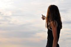 指出天空的被覆盖的女孩 免版税库存照片