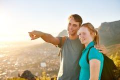 指出某事的年轻人对他的远足的女朋友 免版税库存照片
