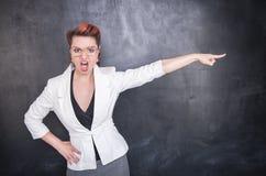 指出黑板背景的恼怒的叫喊的老师 库存照片