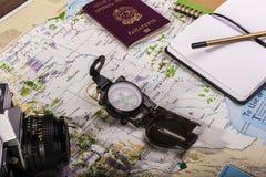 指南针、护照、照片照相机和块笔记关于地图 免版税库存图片