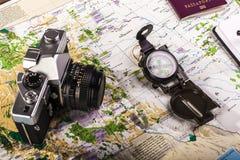 指南针、护照、照片照相机和块笔记关于地图 库存图片