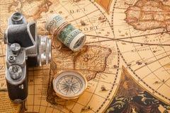 指南针、金钱和一台老照相机在葡萄酒卡片说谎 免版税库存图片