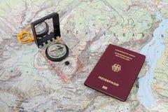指南针和护照在一张远足的地图 库存照片