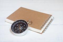 指南针和棕色笔记本在白色木桌背景,旅途计划概念 免版税库存图片