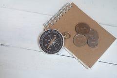 指南针和棕色笔记本在白色木桌背景,旅途计划概念 免版税库存照片