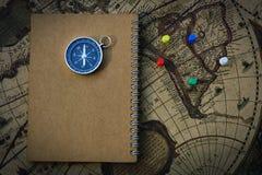 指南针和笔记本在迷离葡萄酒世界地图,旅途概念,拷贝空间 库存图片