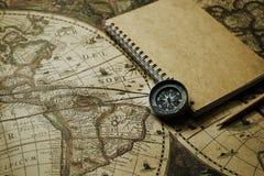 指南针和笔记本在迷离葡萄酒世界地图,旅途概念,拷贝 免版税图库摄影