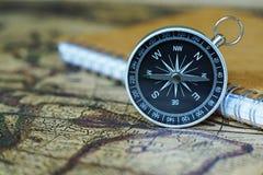 指南针和笔记本在迷离葡萄酒世界地图,旅途概念 库存图片