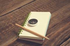 指南针和铅笔在笔记薄在木书桌上 免版税库存照片