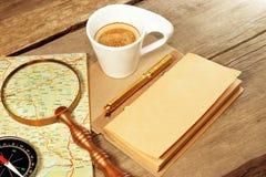 指南针放大器葡萄酒笔记薄金笔咖啡杯木头表 免版税图库摄影