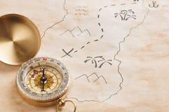 指南针特写镜头在被弄脏的被染黄的纸板料的与一部分的手拉的珍宝地图 免版税图库摄影