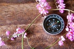 指南针的特写镜头视图在桌上的与桃红色花 免版税库存照片