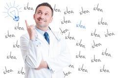指向一个好主意的激动的英俊的成功的医生 免版税图库摄影