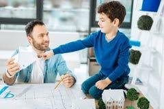 指向一个房子模型的小男孩在父亲手上 免版税库存照片